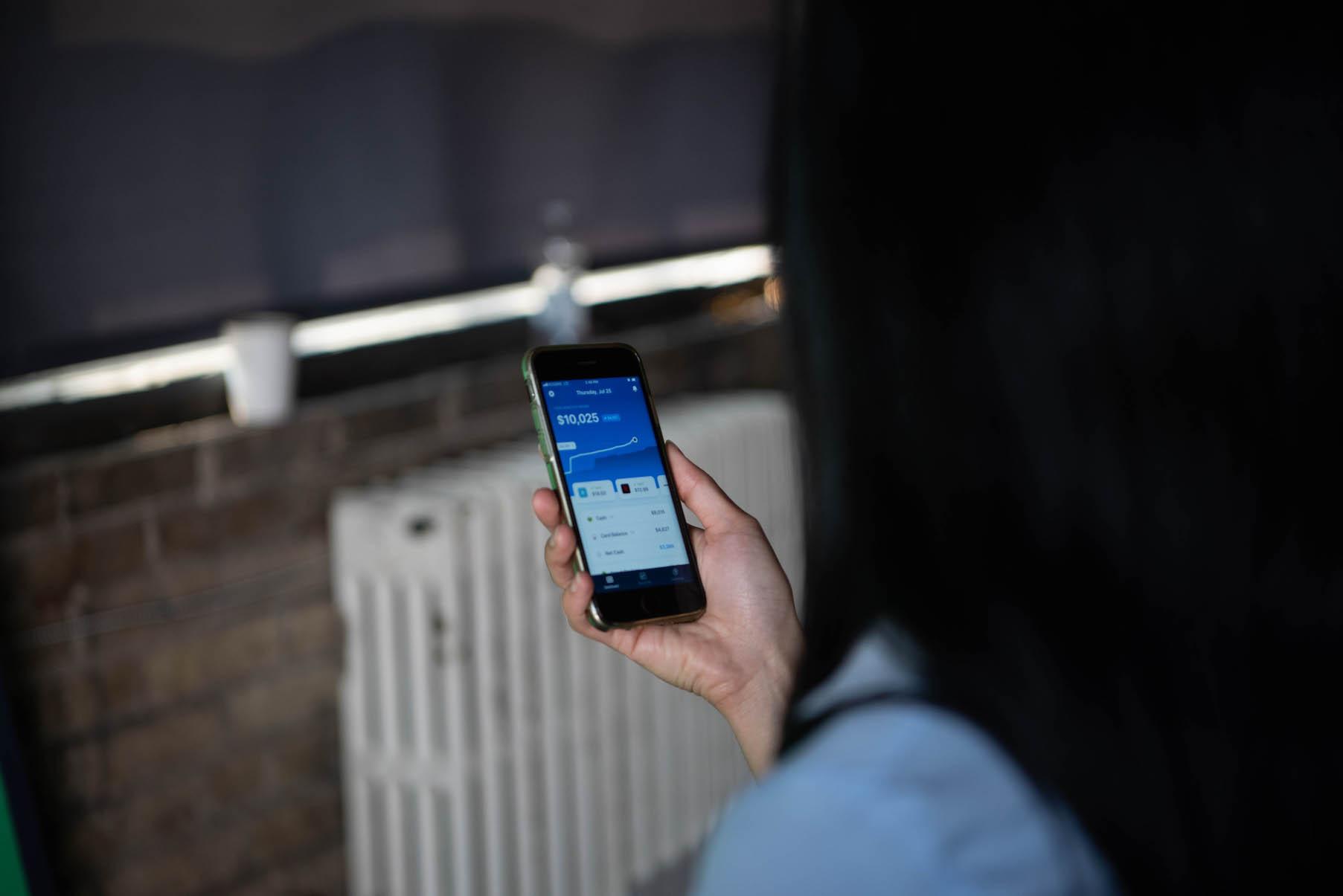 Actress holding smartphone using Truebill app